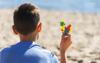 boy-sitting-beach-looking-sea-ocean-holding-colorful-autism-awareness-heart_206881-381